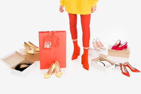 cropped view of girl with red shopping bag and sale tag isolated on white with footwear boxes Stockfoto