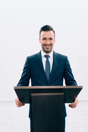 smiling lecturer standing at podium tribune during seminar in conference hall