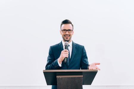 lachende spreker gebaren en praten in microfoon op podium tribune tijdens seminar in conferentiezaal Stockfoto