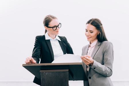 beautiful assistant showing documents to attractive speaker during seminar in conference hall Фото со стока