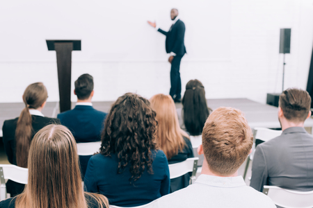selective focus of african american lecturer talking to audience during seminar in conference hall