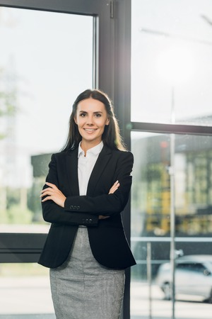 portrait of smiling businesswoman with arms crossed standing in conference hall
