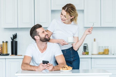 happy young man using smartphone and looking at smiling girlfriend drinking coffee at morning Imagens