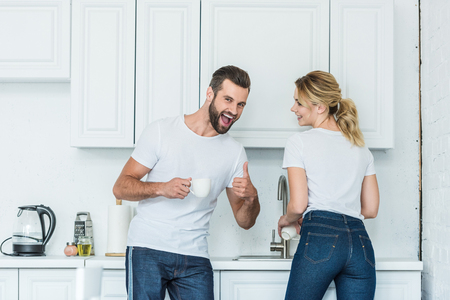 cheerful young couple laughing together in kitchen, man showing thumb up and smiling at camera