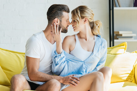 happy passionate young couple able to kiss on sofa at home