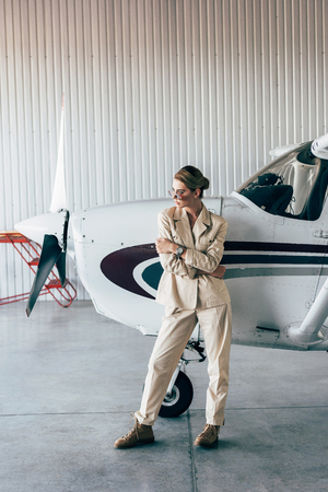 fashionable woman in sunglasses and jacket posing near aircraft in hangar