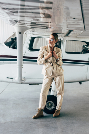attractive stylish woman in sunglasses and jacket posing near aircraft in hangar