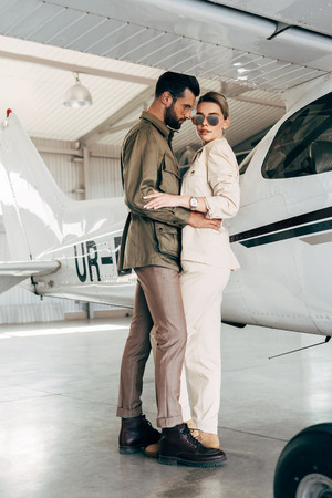 stylish young couple in jackets embracing near airplane in hangar