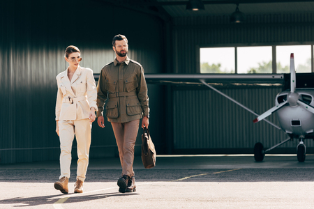 serious man carrying bag and walking with stylish girlfriend near hangar with plane