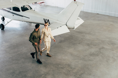 high angle view of young couple in stylish jackets walking in hangar with airplane
