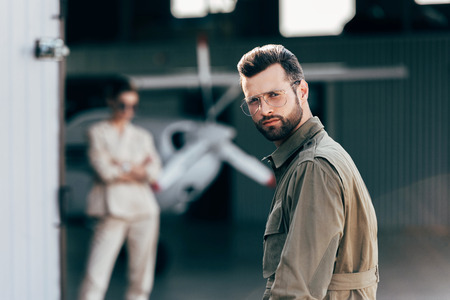 portrait of handsome man in eyeglasses and jacket looking at camera while his girlfriend standing in hangar with plane Stock Photo