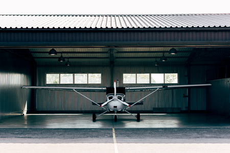 small modern white airplane standing in hangar Stock Photo