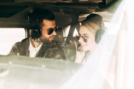 male pilot in headset and sunglasses talking to girlfriend in cabin of airplane Banco de Imagens