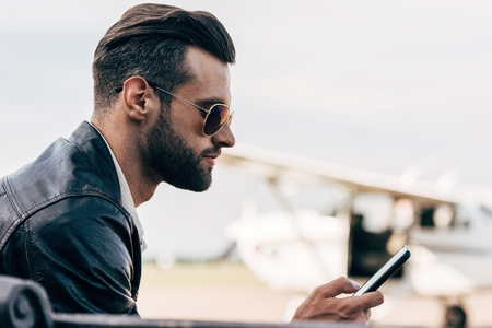 side view of stylish man in leather jacket and sunglasses using smartphone 免版税图像