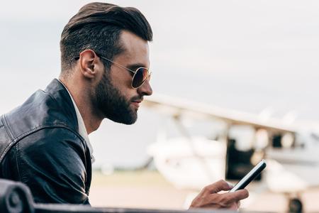vista laterale dell'uomo elegante in giacca di pelle e occhiali da sole utilizzando smartphone