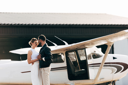 stylish couple in sunglasses embracing and standing face to face near airplane