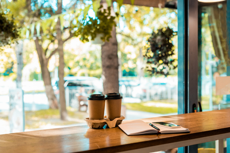 two coffee in paper cups, open notebook with pen on cafe counter