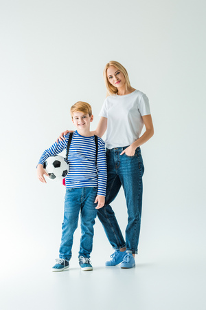 cheerful mother and son standing with football ball on white and looking at camera Banco de Imagens