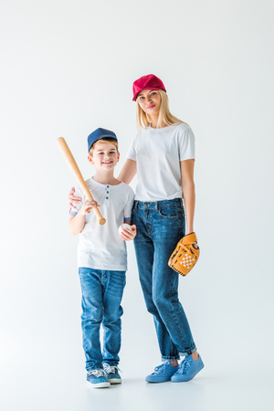 mother and son looking at camera and holding baseball bat, glove and ball on white