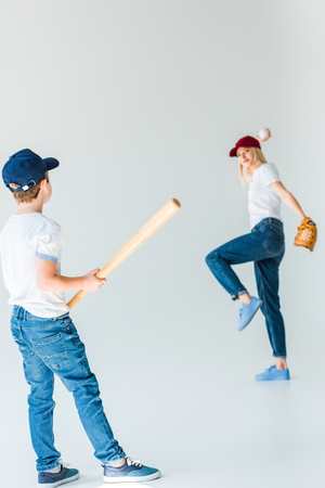 mother and son playing baseball isolated on white