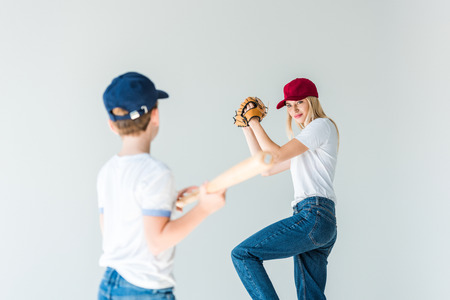mother pitching baseball ball to son with baseball bat isolated on white