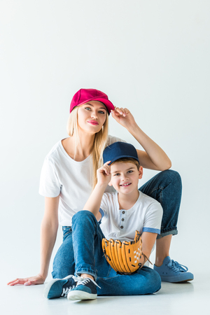 mother and son touching caps and sitting on floor with baseball glove on white Stockfoto