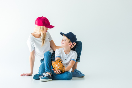 mother and son in caps sitting on floor with baseball glove on white and looking at each other
