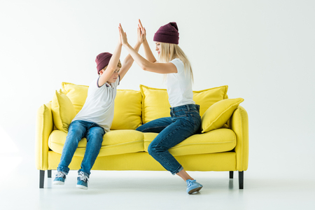 mother and son in burgundy hats giving high fives on yellow sofa on white