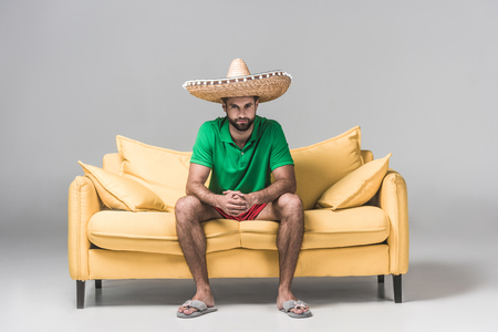 handsome bearded man in mexican sombrero on yellow sofa on grey