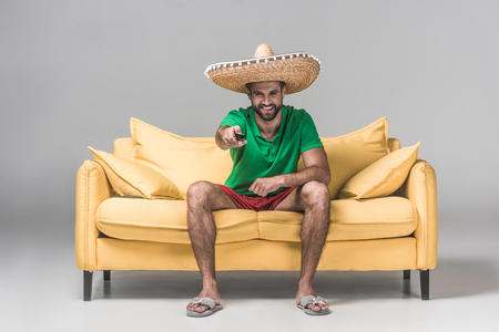 smiling bearded man in mexican sombrero watching TV with remote control on yellow sofa on grey Stock Photo