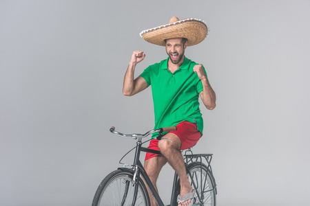 cheerful man in mexican sombrero celebrating and sitting on bike on grey Stock Photo