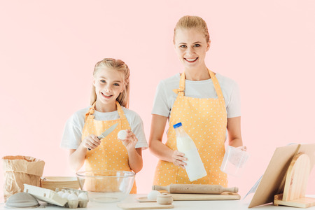 happy mother and daughter looking at camera while preparing dough isolated on pink Banque d'images
