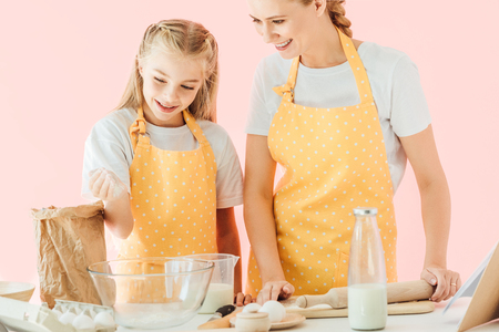 happy attractive mother and daughter with flour cooking together isolated on pink