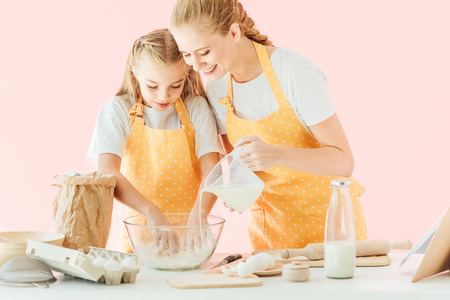 happy mother pouring milk into dough while daughter kneading isolated on pink