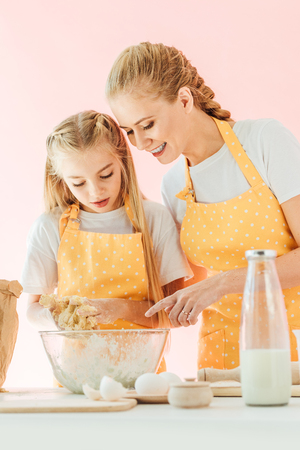 happy mother teaching daughter how to knead dough isolated on pink