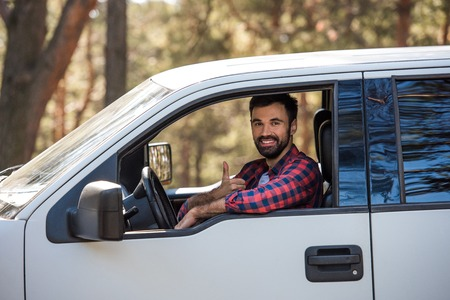 bearded driver showing thumb up while sitting in pickup truck in forest Zdjęcie Seryjne