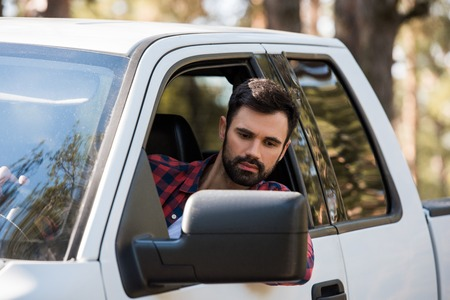 handsome bearded man driving pickup truck in forest Stock Photo