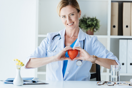 happy female doctor in white coat showing heart symbol at table in office