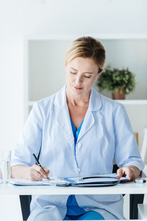 focused female doctor in white coat writing in clipboard at table in office Stok Fotoğraf