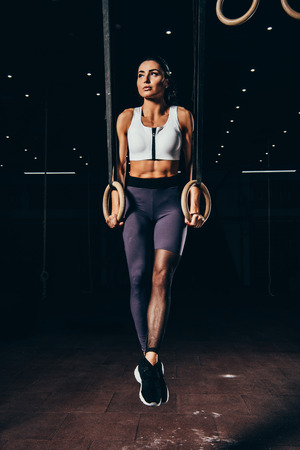 attractive athletic sportswoman exercising with gymnastic rings