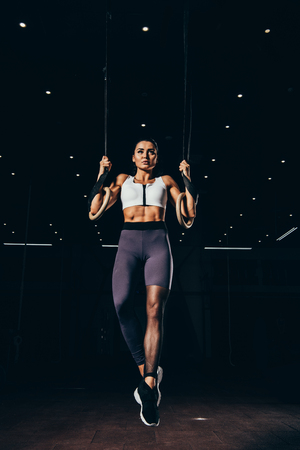 attractive sporty woman exercising with gymnastic rings