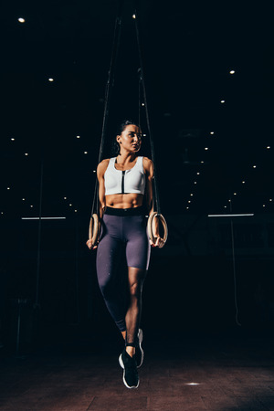 beautiful fit sportswoman working out with gymnastic rings