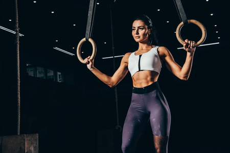 attractive fit sportswoman working out with gymnastic rings Фото со стока