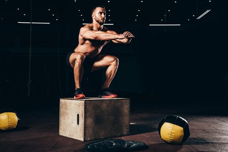 handsome athletic bodybuilder doing squats on cube in dark gym Stock Photo