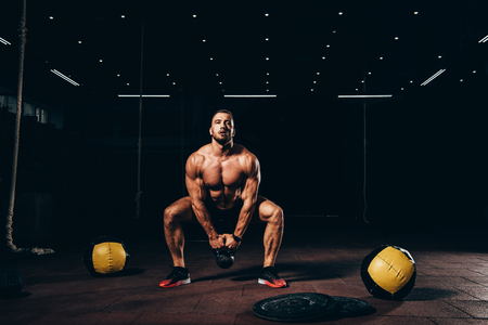 handsome athletic bodybuilder doing squats with kettlebell in dark gym Stock Photo - 110379253