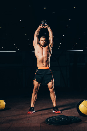 handsome muscular man holding kettlebell overhead while working out  in dark gym Imagens - 110379254