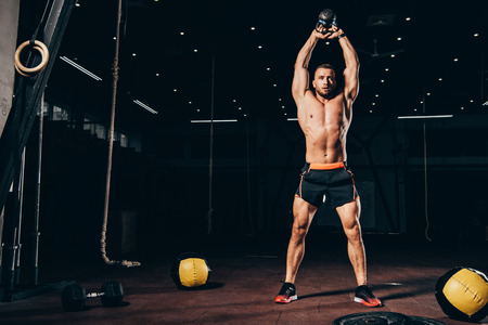 handsome athletic man holding kettlebell overhead while working out  in dark gym