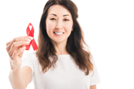 close-up portrait of happy adult asian woman holding aids awareness red ribbon isolated on white Stock Photo