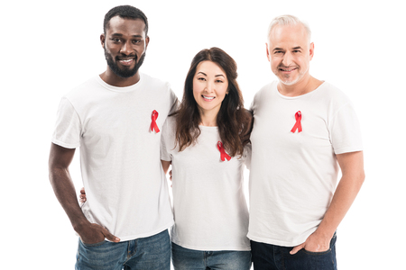 multiethnic group of people in blank white t-shirts with aids awareness red ribbons embracing and looking at camera isolated on white Imagens