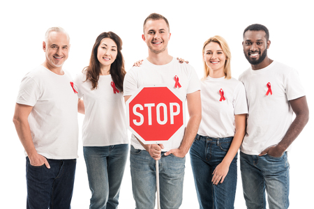 group of people in blank white t-shirts with aids awareness red ribbons and stop road sign looking at camera isolated on white